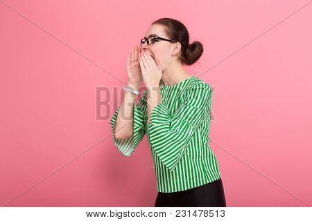Portrait Of Attractive Businesswoman With Hair Bun In Striped Blouse And Eyeglasses Shouting Aside W