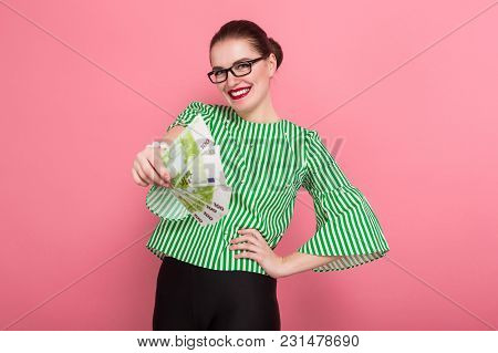 Portrait Of Happy Businesswoman With Hair Bun In Striped Blouse And Eyeglasses Holding Fan Of Euro B