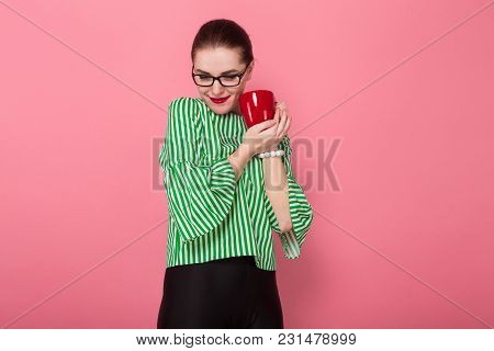 Portrait Of Attractive Businesswoman With Hair Bun In Striped Blouse And Eyeglasses Holding Red Mug