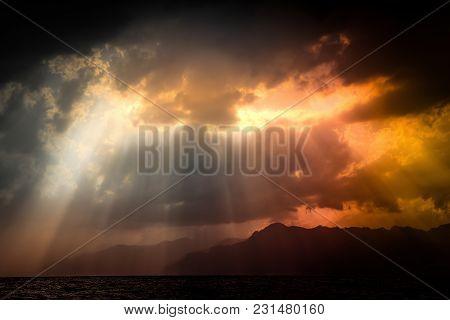 Black Stormy Sky Over Tyrrhenian Sea And Mountains Silhouette With Orange Sun Rays Shining Through C