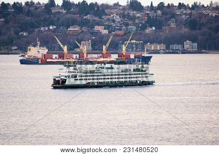 March 7, 2018 In Seattle, Wa:  Ferry Vessel Departing Seattle For Bainbridge Island With A Freighter