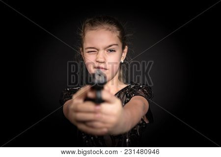 Young Girl In A Dress Aims A Gun At The Camera, On A Black Background