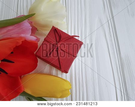 bouquet of tulips on a white wooden background, gift box