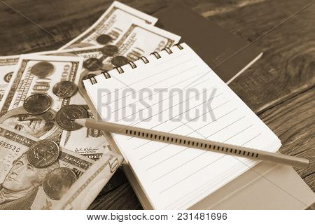 Dollars And Passport Lying On Wooden Table. Notepad To Plan. Copy Paste