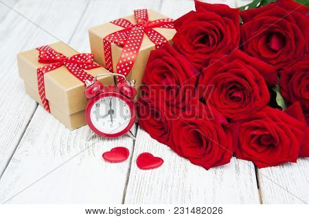 Beautiful Bouquet Of Roses With A Gift Box On A Wooden Background