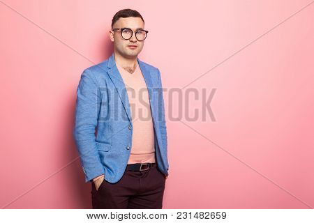 Portrait Of Handsome Man In Eyeglasses, Pink Jumper And Blue Jacket Holding Hands In Pockets Isolate