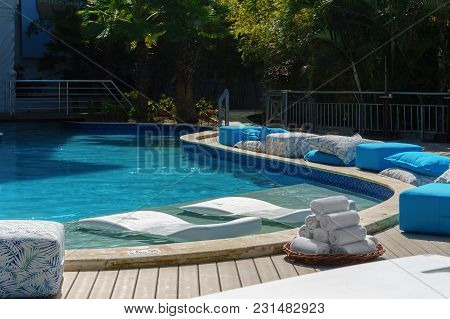 Luxury Elite Resort, Relaxation Place By The Blue Pool With Daybeds, Ottomans And White Towels