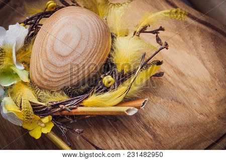 Wooden Egg In A Wreath Of Feathers, Easter Holiday Background