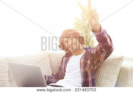 happy guy with laptop sitting on sofa and showing his hand a win