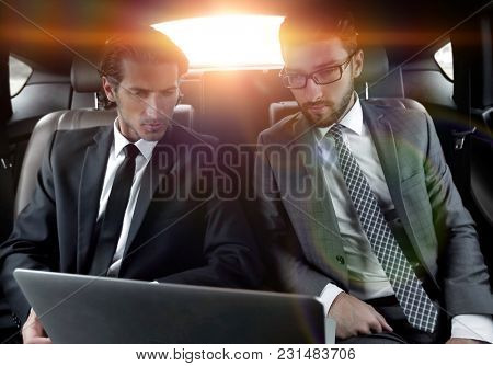 business partners sitting in a luxury car