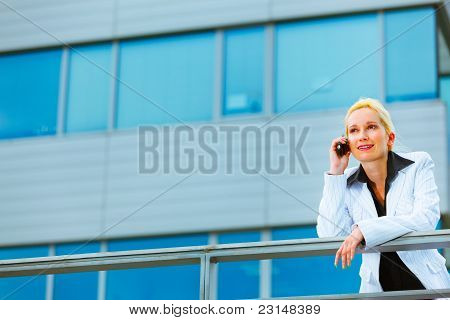 Business Woman Leaning On Railing At Office Building And Talking Mobile