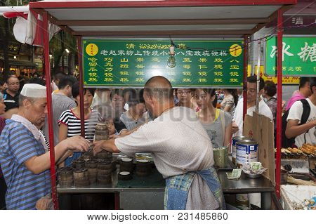 Xian, China - August 5, 2012: People Buying Food In A Food Stall At A Street Market At The Muslim Qu