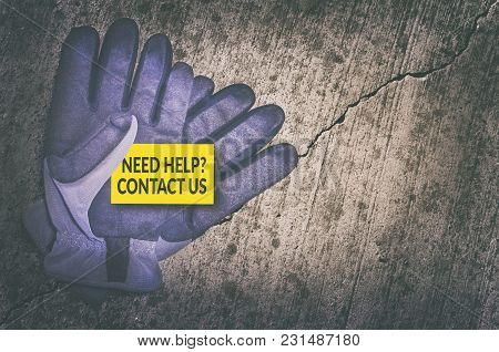 Need Help? Contact Us Card In Protective Gloves On Cracked Concrete Background.