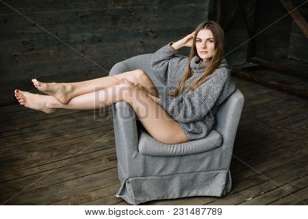 Cheerful Woman In Long Grey Knitted Cozy Sweater Sitting On The Grey Chair With Raised Legs On A Dar