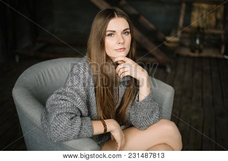 Dark Haired Sad Woman In Long Grey Knitted Cozy Sweater Sitting In A Chair At Home Near Big Window.