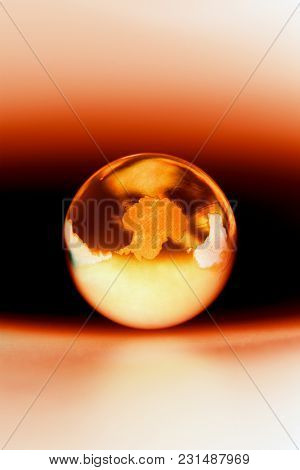 Translucent glass globe showing Antarctica, concept of global warming.