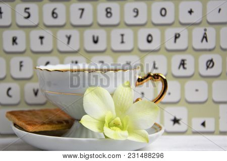 Vintage Coffee Cup With Espresso On A Saucer, Biscuit, Green Orchid Flower And Imitation Of Keyboard