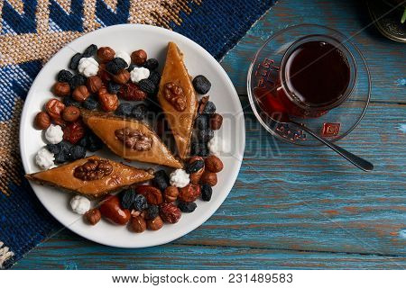 Plate With National Pakhlava And Snacks For Novruz With Glass Of Tea On Wooden Table, Close-up