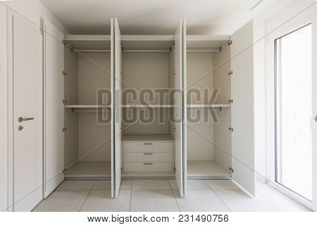 Empty room with large wardrobe and window. Nobody inside
