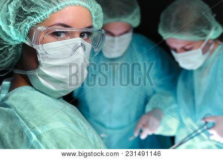 Closeup Of Surgeons Performing Operation. Focus On Female Nurse. Medicine, Surgery And Emergency Hel