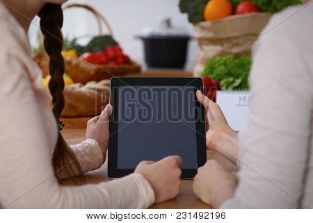 Closeup Of Human Hands Cooking In Kitchen. Women Discuss A Menu Using Tablet Computer. Copy Space Ar