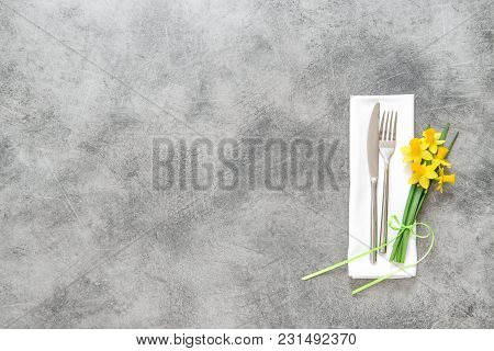 Fork, Knife And Napkin Over Table Background With Spring Narcissus Flowers Decoration