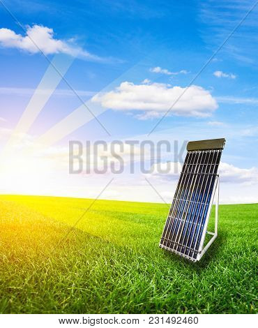 Solar Panel Battery On The Field With Green Grass Blue Sky And Rays Of The Setting Sun.