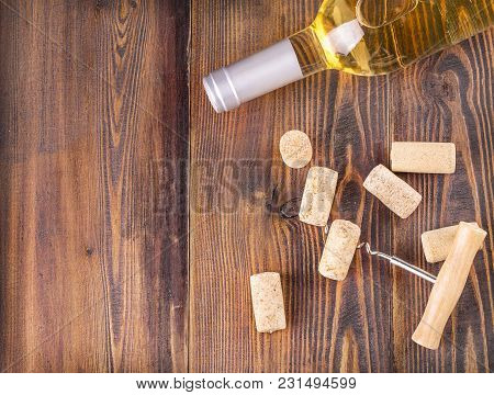 Wine Bottle, Corkscrew And Stopper On Wooden Surface