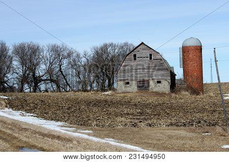 A Abandoned Barn And Silo On A Abandoned Farmstead Against A Blue Sky.