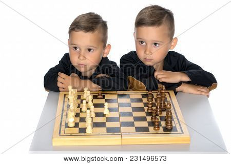 Two Brothers Are Playing Chess At Home. Game, Education, Lifestyle Concept.isolated On White Backgro