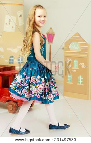 Beautiful Little Girl With Long Blond Hair In A Smart Blue Dress. Girl Playing With A Toy Wooden Car