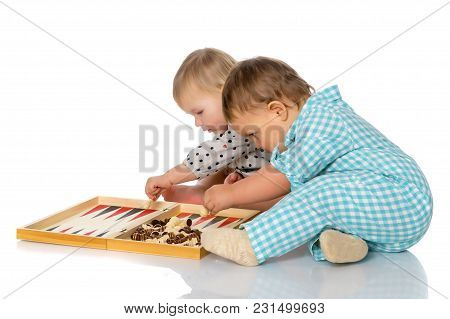 Baby Boy And Girl, Play Chess Or Backgammon. The Concept Of A Harmonious Development Of A Child In T