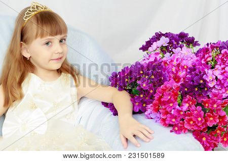 A Lovely Little Girl With Long, Luxurious, Blond Hair In A White Ball Gown.on The Couch With A Bouqu