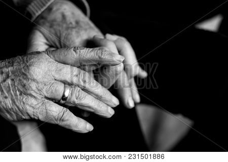 closeup of an old caucasian woman holding the hand of a young caucasian man, with their fingers entwined with affection, in black and white