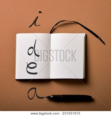 high angle view of an open notepad and a black marker pen, and the worid idea written with it