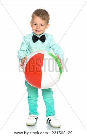 A Cheerful Little Boy Is Playing With A Ball In The Studio On A White Background. The Concept Of A H