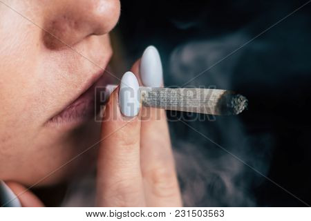 Cannabis Weed, A Joint In His Hands A Woman Smokes . Smoke On A Black Background. Concepts Of Medica
