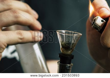 Bong Lighter For A Man Smokes Cannabis Weed, In His Hands. Smoke On A Black Background. Concepts Of