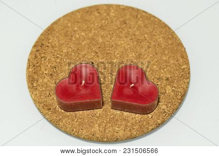 Two Heart Shaped Red Candles On Round Cork Hot Pad On White Background
