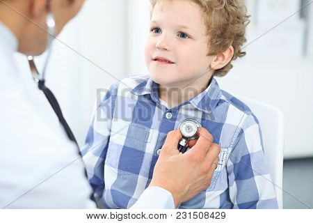 Doctor And Child Patient. Physician Examines Little Boy By Stethoscope. Medicine And Children's Ther