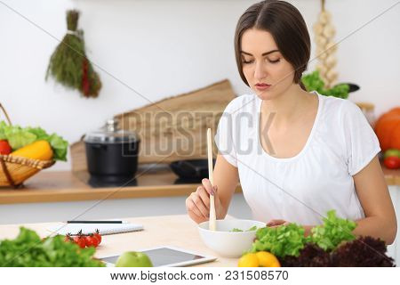 Beautiful  Hispanic Or Latin American Woman Is Holding Wooden Spoon While Cooking In The Kitchen. Br