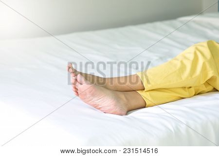 Woman Legs And Feet Of Relaxing On A Bed After Long Journey Traveler Sleeping On Hotel Room Bed.