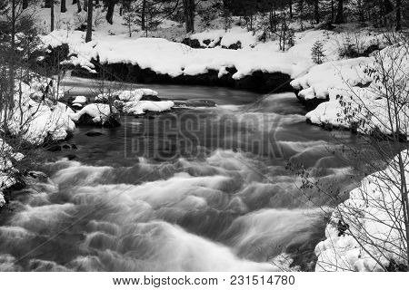 The Rogue River Is Flowing Unfrozen Creating Whitecaps Deep In The Forest In Winter