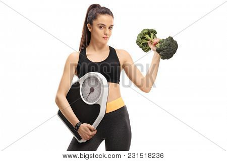Fitness girl holding a weight scale and a broccoli dumbbell isolated on white background