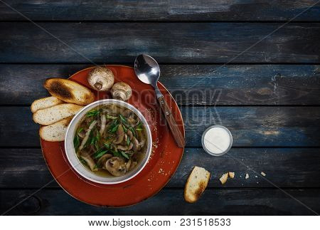 Fresh Mushroom Soup With Green Onion Sour Cream And Bread Crisps. On A Ceramic Plate. Colored Wooden
