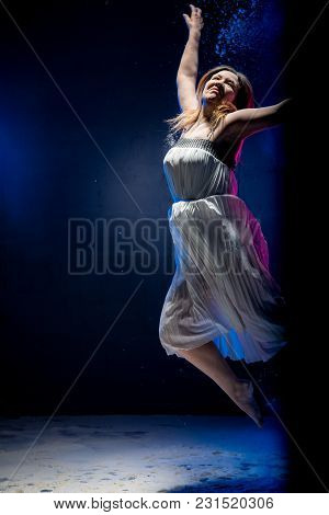 Old Fat Ballerina Tries To Dance In The Studio During Photoshoot With Flour On A Black Background Wi