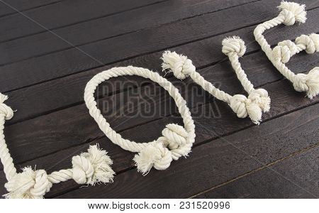 The Word: Love With Rope On Wooden Background