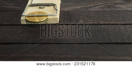 Bitcoin In A Dusty Old Mouse Trap With Dust On Wooden Background