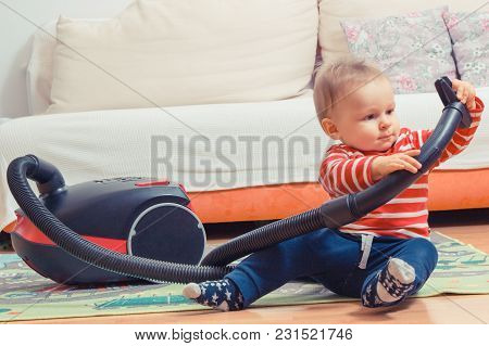 Little Baby Boy Sitting On Carpet At Home And Playing With Pipe Of Vacuum Cleaner With Brush