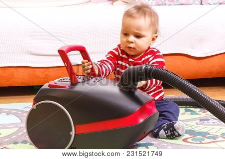 Little Baby Boy Sitting On Floor And Playing With Vacuum Cleaner